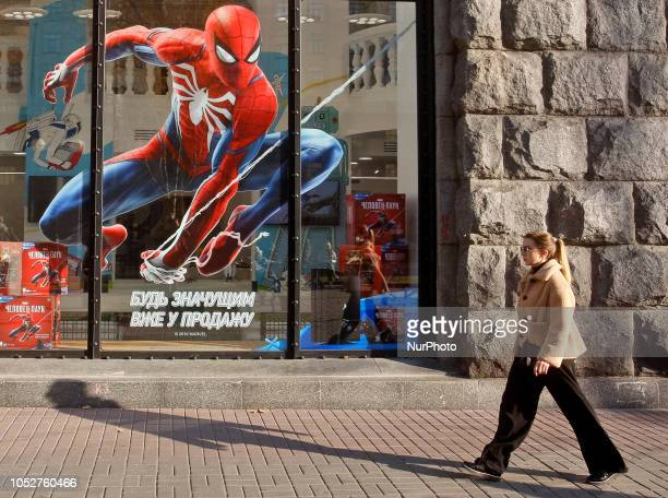 An Ukrainian woman walks in front of the SpiderMan advertisement seen in a shop window in a sunny day in Kiev Ukraine 22 October2018