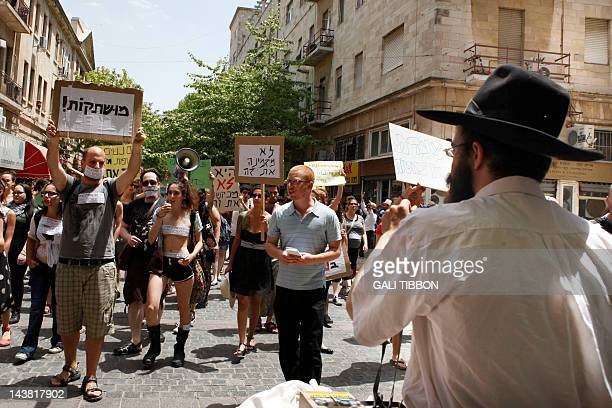 An Ultra Orthodox Jew looks at Israeli activists taking part in a 'SlutWalk' rally in Jerusalem on May 4 2012 to protest sexual violence and counter...