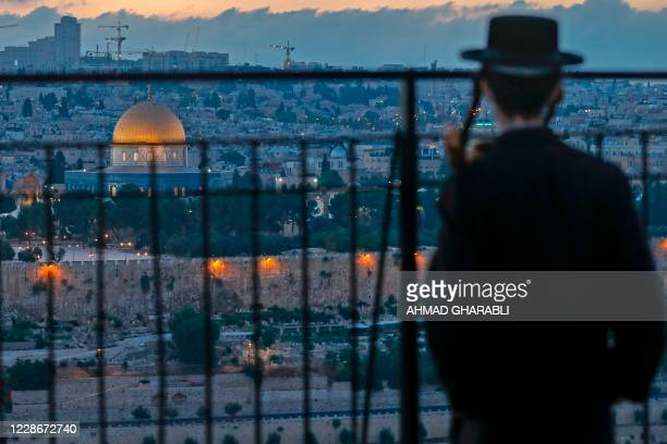 An Ultra Orthodox Jew looks from a spot on the Mount of Olives towards Jerusalem's Old City, with a view of the Dome of the Rock in the al-Aqsa...