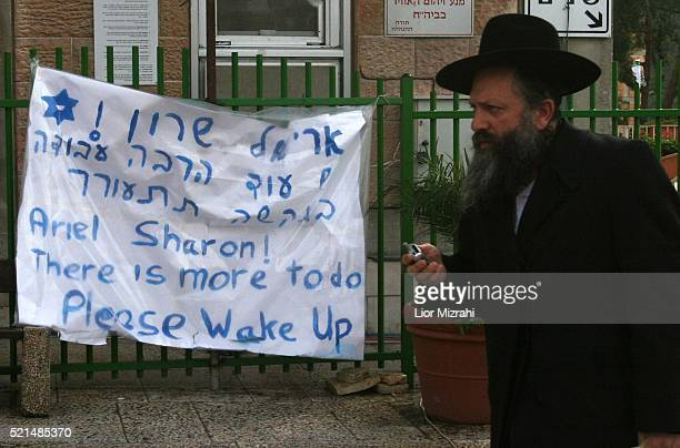 An ultra orthodox Jew man passes by a poster wishing Israeli Prime Minister Ariel Sharon a quick recovery and return to work at the entrance of...