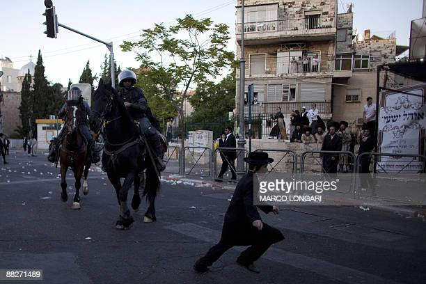 An ultra Orthodox Jewish boy runs away from charging Israeli mount policemen during a demonstration in the conservative Jerusalem district of Mea...