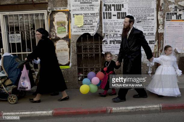 An Ultra Orthodox Jewish family dressed up in costumes walk with balloons in the Ultra Orthodox neighborhood of Mea Shearin as they celebrate the...