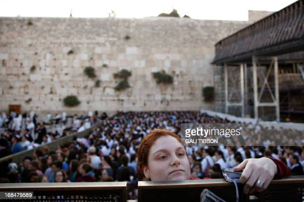 An Ultra Orthodox Jewish girl looks at members of the liberal eral Jewish religious group Women of the Wall on May 10 2013 at the Western Wall in...