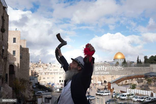 An Ultra Orthodox Jewish man holds a shofar with the golden Dome of the Rock Islamic shrine behind on December 6 2017 in Jerusalem Israel US...