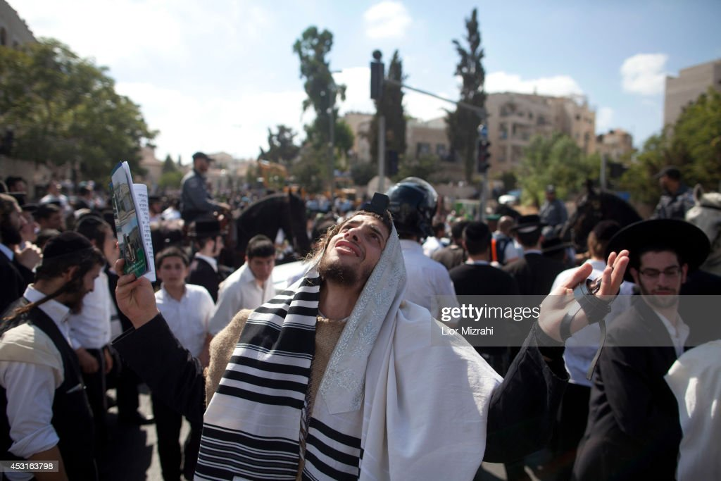 An Ultra Orthodox Jewish man prays near where a Palestinian man rammed an excavator into a bus on August 04, 2014 in Jerusalem, Israel. The man driving the excavator used the machinery to flip over a bus, killing one. In a seperate incedent, a gunman on a motorcycle opened fire August 4, on a hitchhiking station near Jerusalem's Hebrew University on Mt. Scopus. Several people were wounded in both attacks.