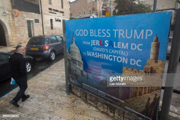 An Ultra Orthodox Jewish man walks next to a poster blessing US President Donald Trump in downtown on December 6 2017 in Jerusalem Israel US...