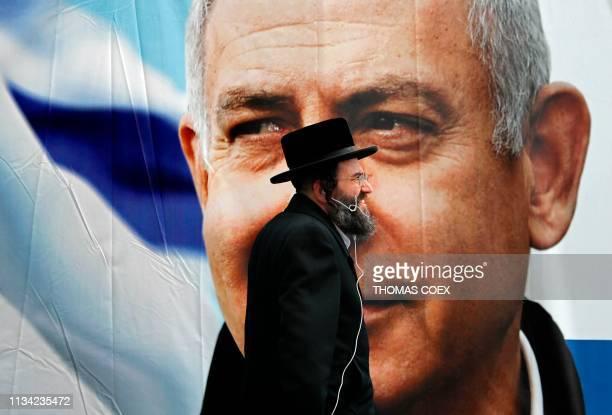 An Ultra Orthodox Jewish man walks past an electoral billboard bearing a portrait of Israel's Prime Minister Benjamin Netanyahu in Jerusalem on April...