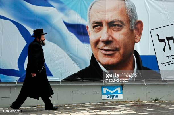 TOPSHOT An Ultra Orthodox Jewish man walks past an electoral billboard bearing a portrait of Israel's Prime Minister Benjamin Netanyahu in Jerusalem...