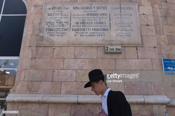An Ultra Orthodox Jewish man walks under a dedication plaque in honor of King George V in King George street in downtown on June 25 2018 in Jerusalem...