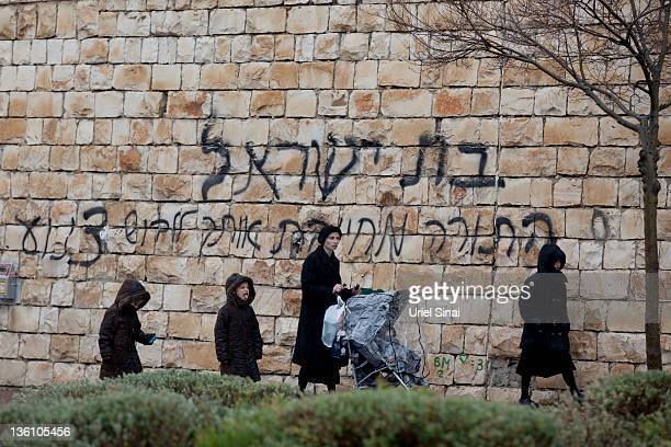 An Ultra orthodox Jewish woman and her children walk past a graffiti that calls Jewish women to dress in a modest way on December 25, 2011 in Beit...