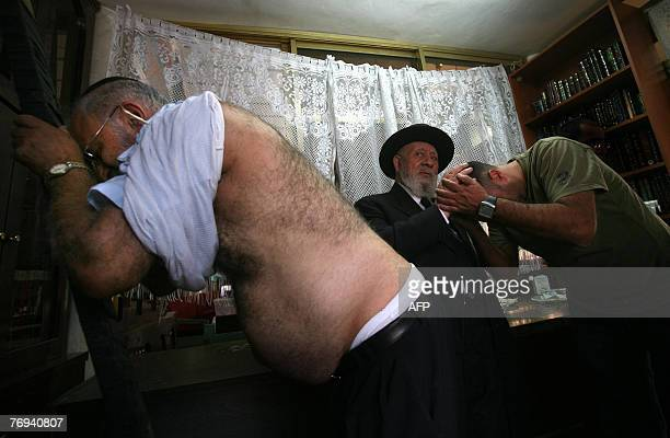 An Ultra Orthodox Rabi David Nisnof of the Bokharan Jewish community bless a man before whips him and orther man with leather straps as a symbolic...