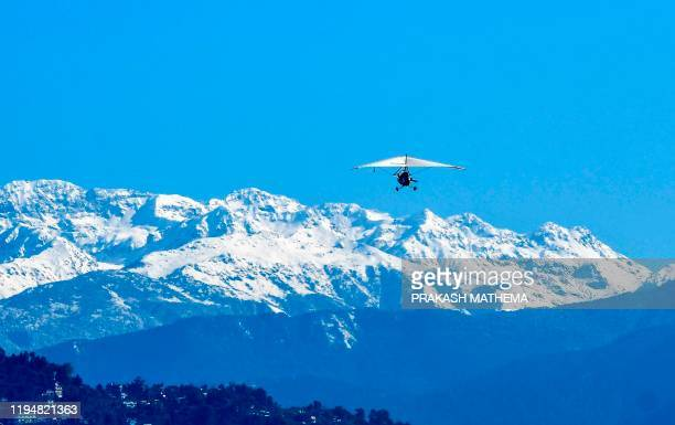 An ultralight aircraft flies above the Annapurna mountain range, in Pokhara, some 200 kms west of Kathmandu on January 20, 2020. - Rescuers...