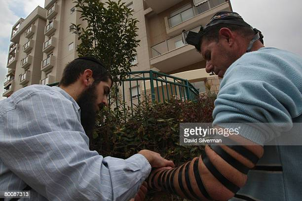 An ultraOrthodox Jew helps an Israeli man put on phylacteries to recite prayers outside an apartment building which was struck a while earlier by a...