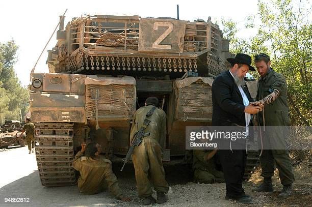 An ultraorthodox Jew helps an Israeli soldier to put on tefillin for prayer while Israeli troops park a tank close to the IsraeliLebanese border near...