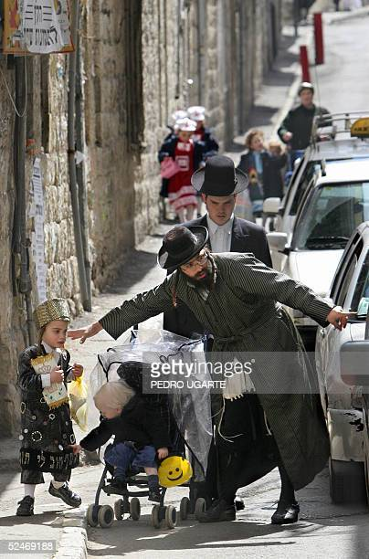 An ultraOrthodox Jew helps his son after a school party prior to the celebration of the Jewish holiday of Purim in Jerusalem's religious neighborhood...