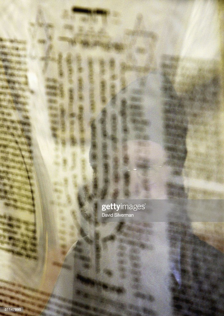 An ultra-Orthodox Jew is reflected in the glass frame as he reads fro a mystical prayer in the cave tomb of Rabbi Shimon HaTzadik (Simon the Righteous), one of the earliest high priests of the biblical Second Temple, August 6, 2004, in Jerusalem. Many religious Jews believe that by praying at the graves of the righteous, their souls advocate the prayers in heaven on behalf of the worshippers.