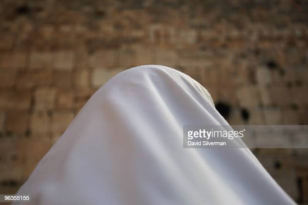 An ultra-Orthodox Jew is wrapped in his Tallit, or prayer shawl, as he recites his daily prayers at the Western Wall on February 2, 2010 in...