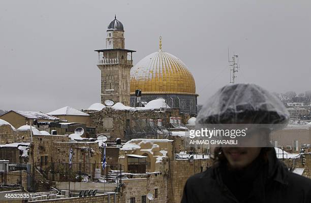 An ultraOrthodox Jew poses for a picture with the Dome of the Rock and the AlAqsa mosque's minaret in the background in the old city of Jerusalem on...