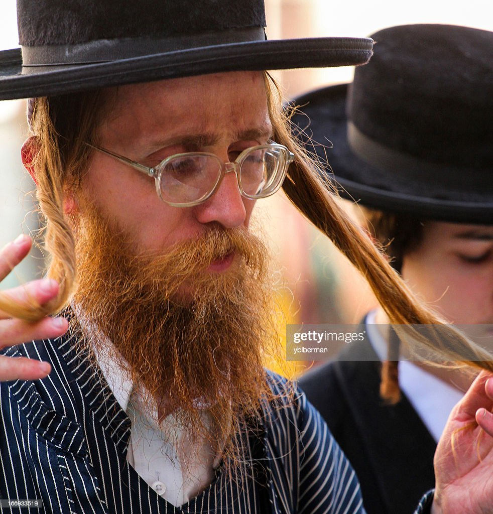An Ultra-Orthodox Jew praying and curling Payot : Stock Photo