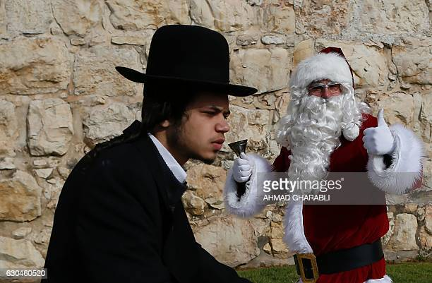 An UltraOrthodox Jew rides past a Palestinian man dressed up as Santa Claus outside Jaffa Gate in Jerusalem's Old City on December 23 as Christians...