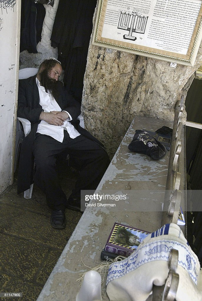An ultra-Orthodox Jew sleeps after praying through the night in the cave tomb of Rabbi Shimon HaTzadik (Simon the Righteous), one of the earliest high priests of the biblical Second Temple, August 6, 2004, in Jerusalem. Many religious Jews believe that by praying at the graves of the righteous, their souls advocate the prayers in heaven on behalf of the worshippers.