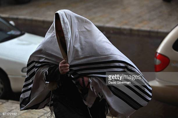 An ultraOrthodox Jew uses his prayer shawl to cover himself from the pouring rain as he runs to Purim festival prayers at the Vishnitz Chassidic...