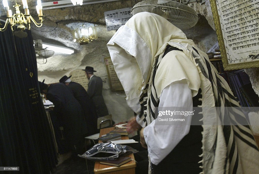 An ultra-Orthodox Jew wears a Tallit (prayer shawl) as he prays in the cave tomb of Rabbi Shimon HaTzadik (Simon the Righteous), one of the earliest high priests of the biblical Second Temple, August 6, 2004, in Jerusalem. Many religious Jews believe that by praying at the graves of the righteous, their souls advocate the prayers in heaven on behalf of the worshippers.