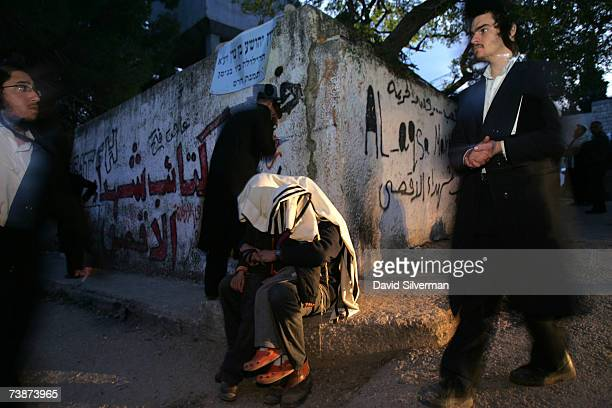 An ultra-Orthodox Jew wraps his two sons under his prayer shawl and blesses them during dawn prayers outside the tomb of the Biblical Israelite spy...