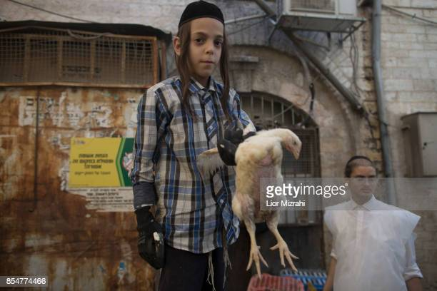 An UltraOrthodox Jewish boy holds a chicken during the Kapparot ceremony on September 27 2017 in Jerusalem Israel It is believed that the Jewish...