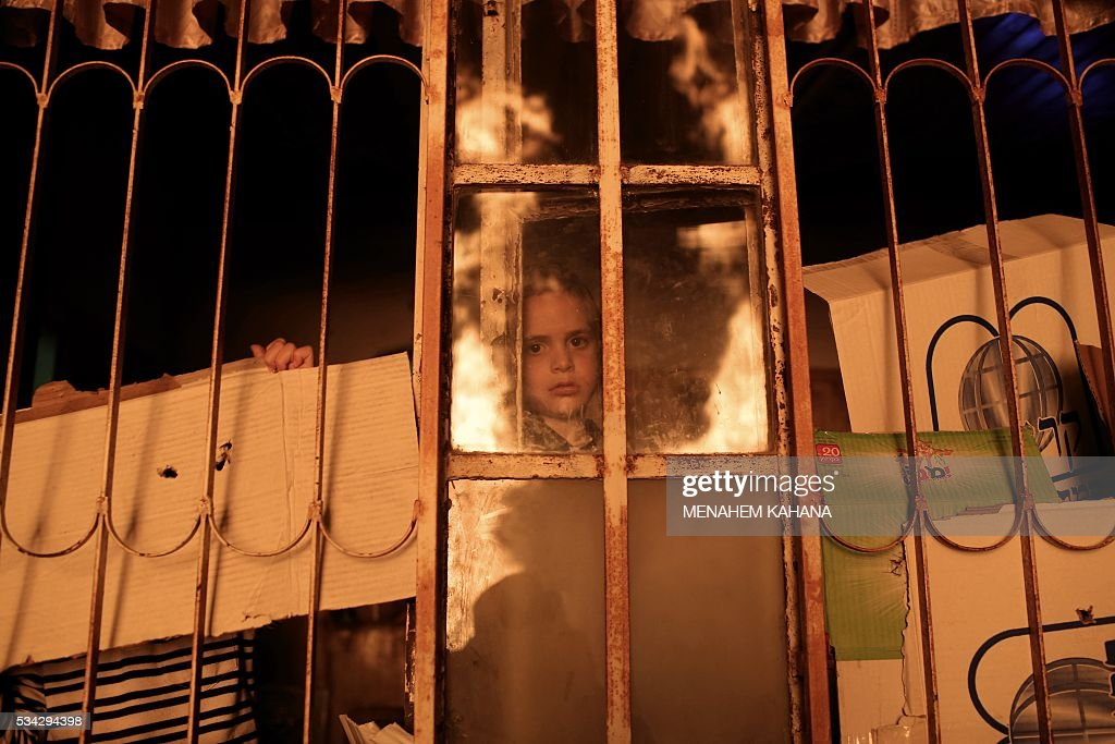 TOPSHOT - An Ultra-Orthodox Jewish boy looks on during the giant bonfire in the Mea Shearim neighborhood of Jerusalem on May 25,2016 during the celebration of Lag BaOmer. The Lag BaOmer bonfire is lit to commemorate the death of renowned Jewish scholar and renowned Bar Yochai some 1800 years ago. In a night long vigil thousands of Jews will light large bonfires and visit the final resting place of Bar Yochai, who is revered as one of Judaism's great sages. / AFP / MENAHEM