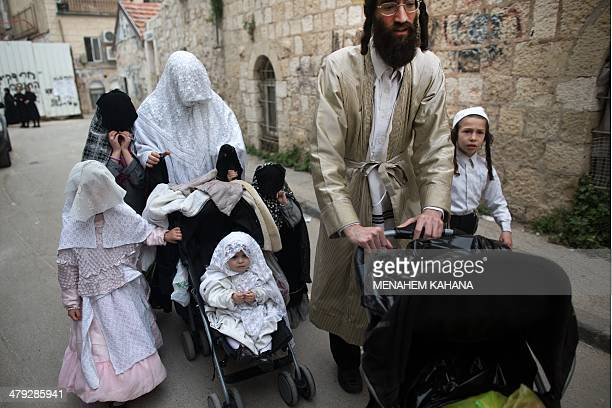 An UltraOrthodox Jewish family dressed in costumes celebrate the Purim holiday in the ultraorthodox Mea Shearim neighborhood in Jerusalem on March 17...