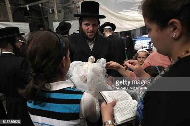 An ultraOrthodox Jewish family hold a chicken as they perform the Kapparot ceremony in the ultraOrthodox neighbourhood of Mea Shearim in Jerusalem on...