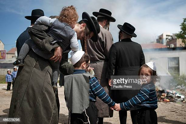 MEA SHEARIM JERUSALEM ISRAEL An UltraOrthodox Jewish family stands in front of a fire where religious Jewish people used to burn leavened items and...