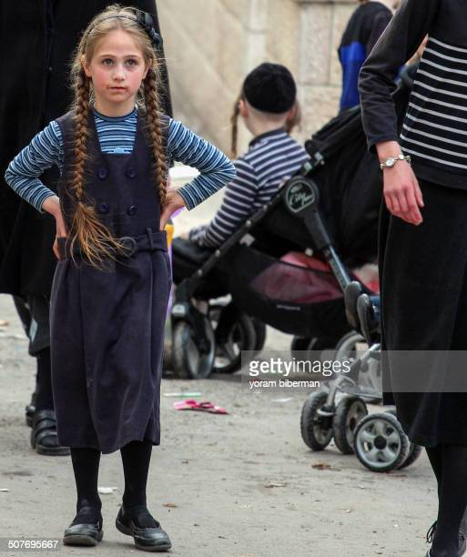 An Ultra-Orthodox Jewish girl, age 10, standing with her hands on her waist. She has blue eyes, blond hair, and very long braids. Photo was taken on...