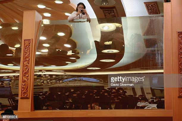 An ultraOrthodox Jewish girl looks over the top of the women's section to take a photograph of the men's section where the Redemption Of The First...