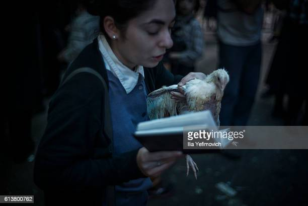 An UltraOrthodox Jewish girl performs the Kaparot ceremony on October 10 2016 in Jerusalem Israel It is believed that the Jewish ritual which...