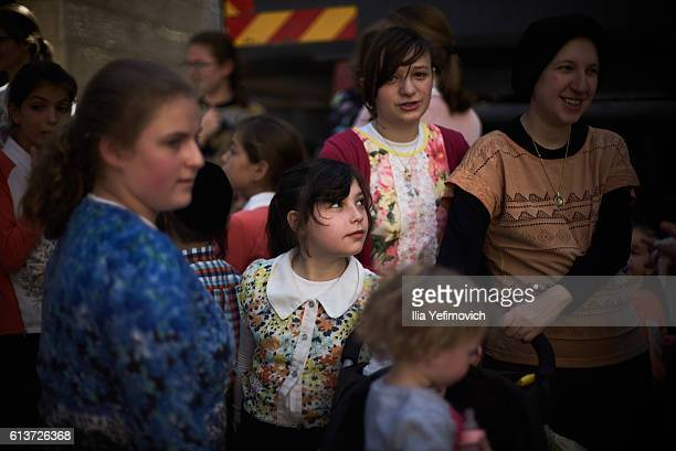 An UltraOrthodox Jewish girl watches as men perform the Kaparot ceremony on October 10 2016 in Jerusalem Israel It is believed that the Jewish ritual...
