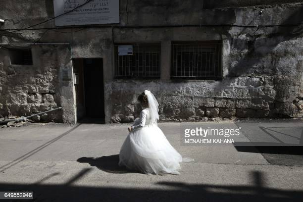 TOPSHOT An ultraOrthodox Jewish girl wearing a bride outfit walks in the street during a school Purim celebration four days ahead of the official...