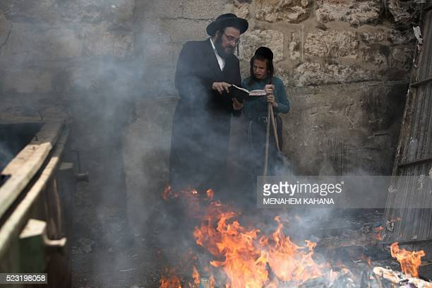 An ultraOrthodox Jewish man and a boy pray as they burn leavened items as part of the Biur Chametz ritual on April 22 2016 in Jerusalem during the...