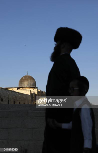 An UltraOrthodox Jewish man and a child walk at the Jewish quarter in Jerusalem's Old City overlooking alAqsa Mosque on September 27 2018 Comments by...