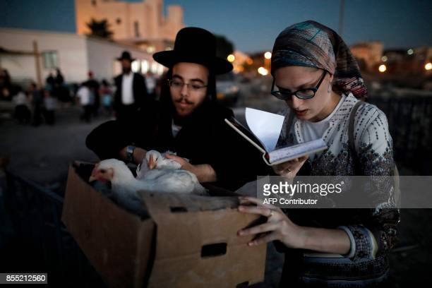 An UltraOrthodox Jewish man and his wife hold chicken as they perform the Kaparot ceremony in the Jewish neighbourhood of Beit Shemesh west of...