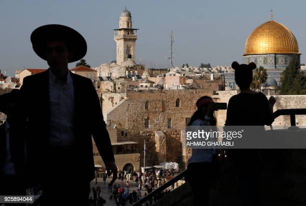 An UltraOrthodox Jewish man and others stand at the Jewish quarter in Jerusalem's Old City overlooking the Dome of the Rock mosque on March 1 2018 /...