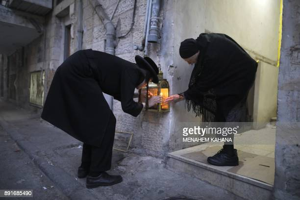 TOPSHOT An ultraOrthodox Jewish man and woman light candles on the second night of the Jewish holiday of Hanukkah in the UltraOrthodox neighbourhood...