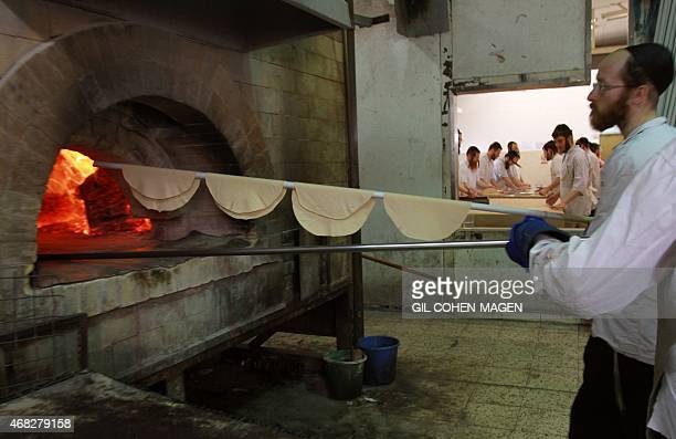 An UltraOrthodox Jewish man bakes the Matzoth during the preparations for the upcoming Jewish Pesach holiday on March 31 2015 in Bnei Brak near the...