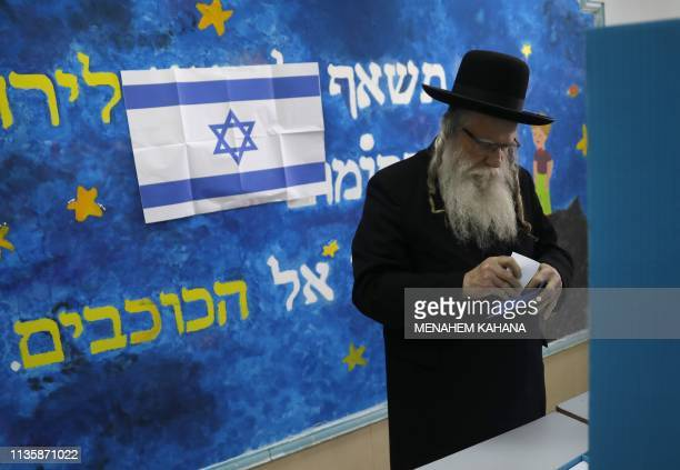 An ultraOrthodox Jewish man casts his vote during Israel's parliamentary elections on April 9 2019 in Jerusalem Israelis voted today in a highstakes...