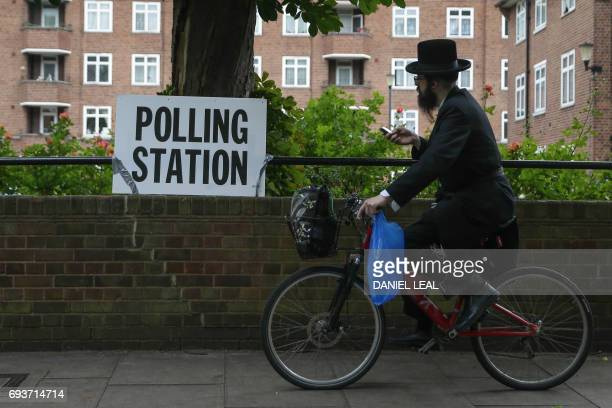 An Ultra-orthodox Jewish man cycles past a polling station sign in northeast London on June 8, 2017as Britain votes in the general election. Polls...