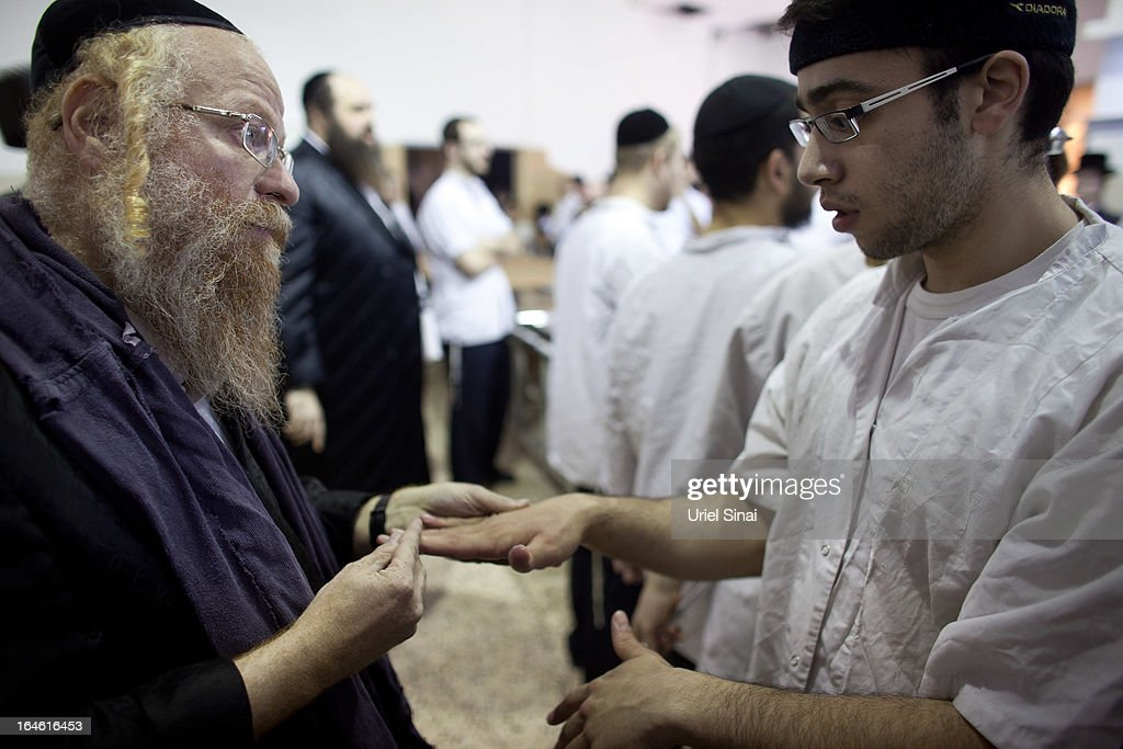 An Ultra-Orthodox Jewish man inspects the hands of a worker before preparing Matzoth, or unleavened bread, in a final preparation before the start at sundown of the Jewish Pesach (Passover) holiday on March 25, 2013 in Bnei Brak, Israel. Religious Jews throughout the world eat matzoth during the eight-day Passover, or Pesach, holiday, The Jewish holiday commemorates the Israelis' exodus from Egypt some 3,500 years ago and their ancestors' plight by refraining from eating leavened food. Passover begins March 25 and ends on the evening of April 02. (Photo by Uriel Sinai/Getty Images