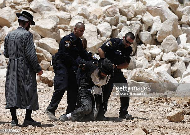 An UltraOrthodox Jewish man is arrested by Israeli policemen during a demonstration against the building of new residence units at a site believed to...