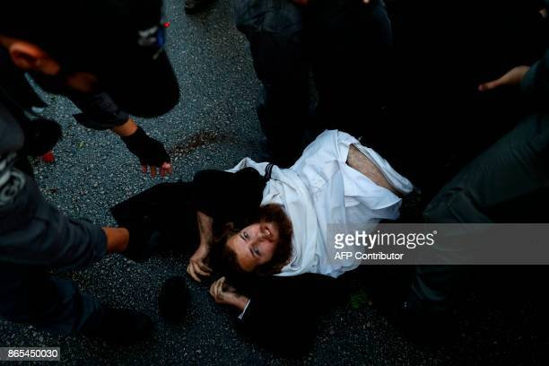 An ultraOrthodox Jewish man lies on the road as security forces try to remove him during a demonstration against Israeli army conscription on October...