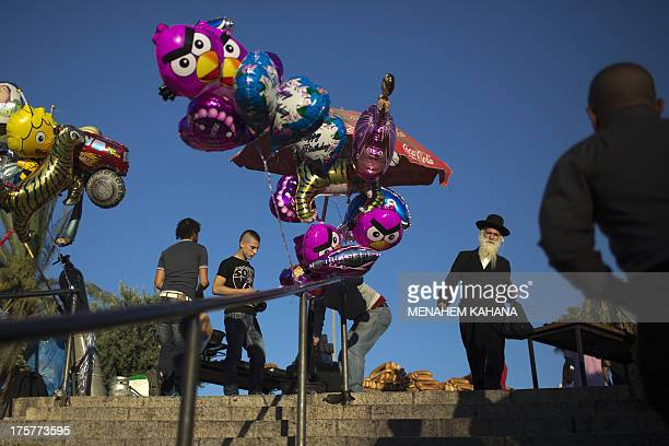 An UltraOrthodox Jewish man passes by a Palestinian street vendor selling balloons at Damascus Gate leading into the old city of Jerusalem as...